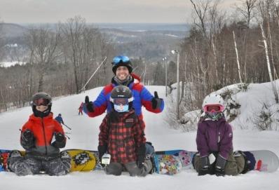 Photo d'une famille qui fait du snowboard